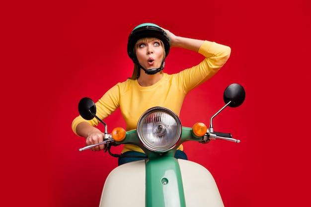 Низкий угол обзора портрет радостной веселой девушки за рулем мопеда с шокированным лицом