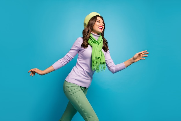 Low angle view profile photo of charming pretty lady traveler walk street excited mood wear green beret hat purple jumper scarf pants isolated blue color wall
