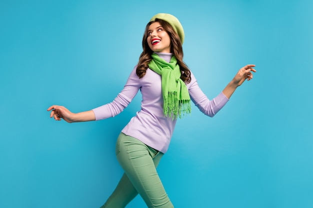 Low below angle view profile photo of charming pretty lady traveler walk street excited mood wear green beret hat purple jumper scarf pants isolated blue color wall