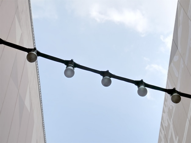 Low angle view of a row of light bulbs with electrical cable