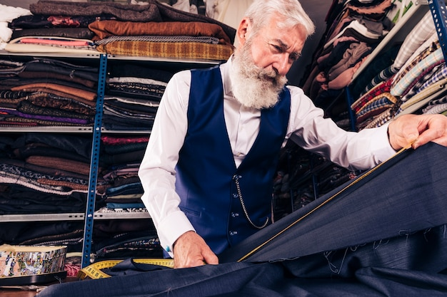 Low angle view of senior male tailor taking measurement of blue fabric with measuring tape