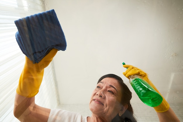 Low angle view of senior woman wiping the glass table with spray