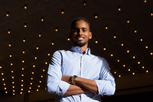 Снимок с низким углом обзора красивого чернокожего африканского бизнесмена на открытом воздухе в городе летом, улыбающегося со скрещенными руками, горизонтальный снимок