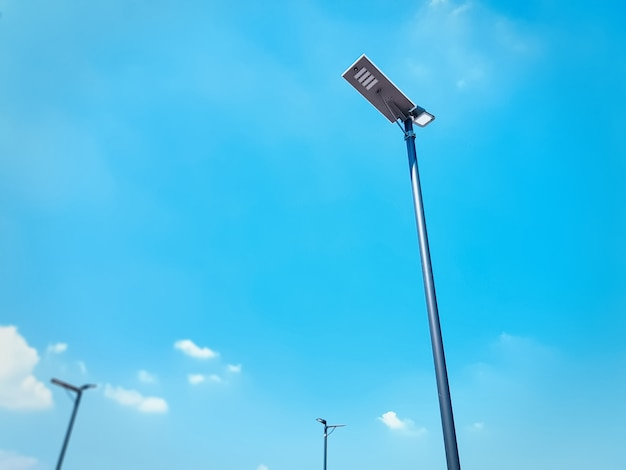 Low angle view of street lighting post against blue sky