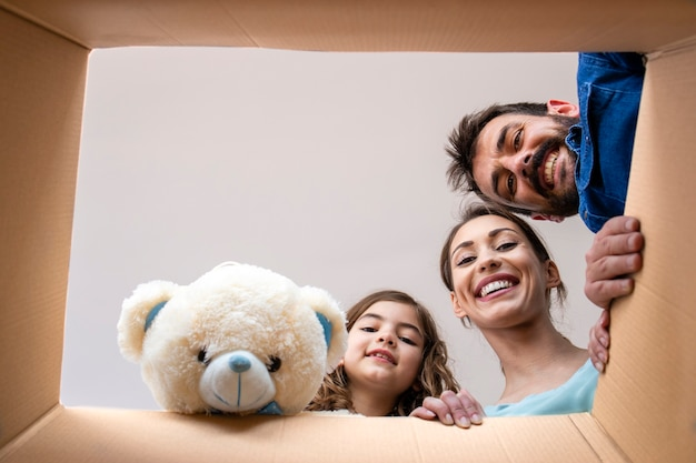 Low angle view through cardboard box of happy family faces and children teddy bear unpacking belongings in new house.