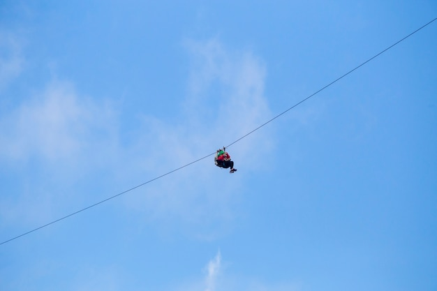 Low angle view of tourist riding a zip line adventure against blue sky