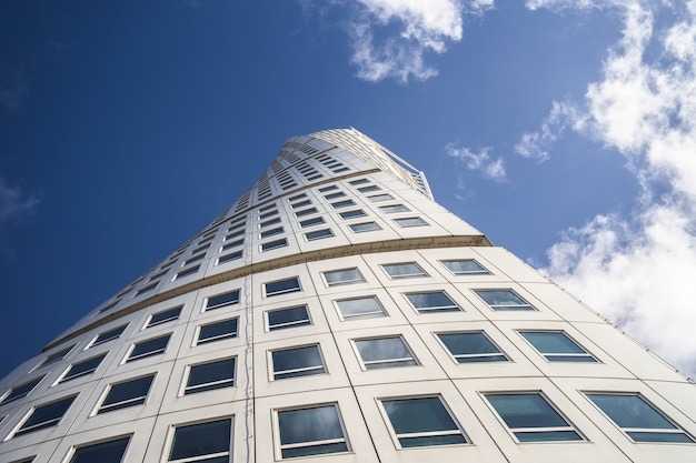 Low angle view of the turning torso under a blue sky and sunlight in malmo in sweden