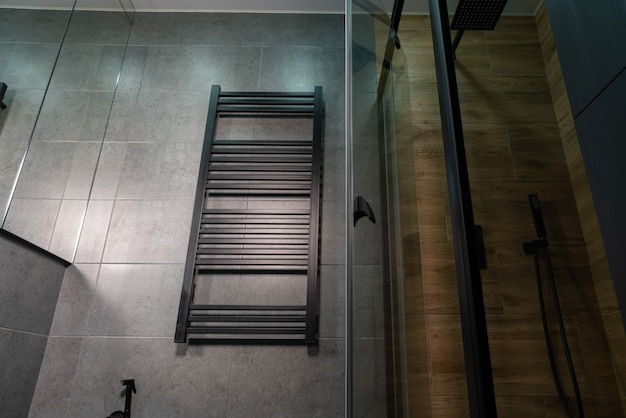 Low angle view of a wall-mounted heated towel rail in a bathroom with grey and wood effect tiles on the walls