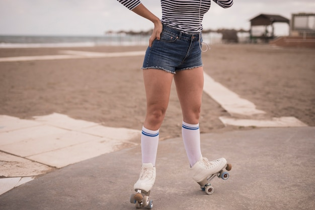 Low angle view of woman balancing on roller skate at beach