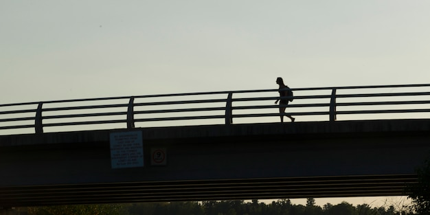 Low angle view of a woman walking on bridge, kenora, lake of the woods, ontario, canada