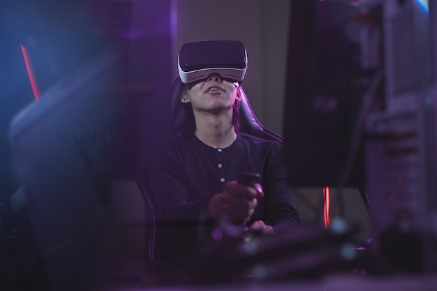 Low angle view at young asian man wearing vr headset while playing videogames using racing shift in dark cyber interior, copy space