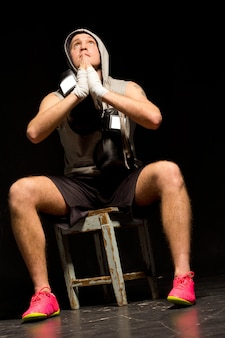Low angle view of a young boxer praying for a victory