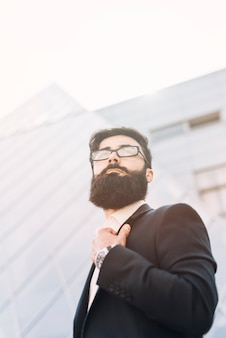 Low angle view of young businessman standing against corporate building