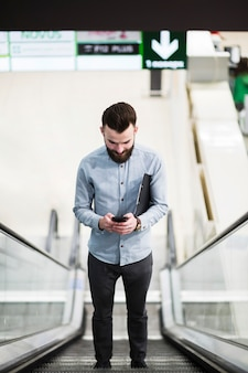 Low angle view of a young businessman standing on escalator using mobile phone