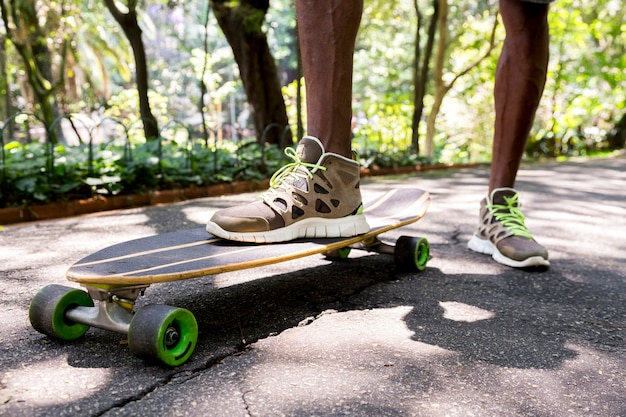 Low angle view of a young male skateboarder's feet in sneakers at park