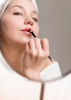 Low angle woman applying lipstick