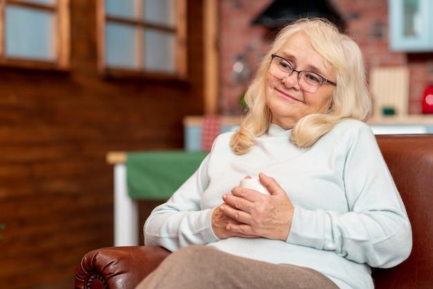 Низкий угол женщина дома пьет чай