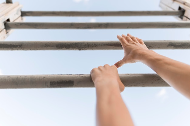 Low angle woman climbing on metal bars