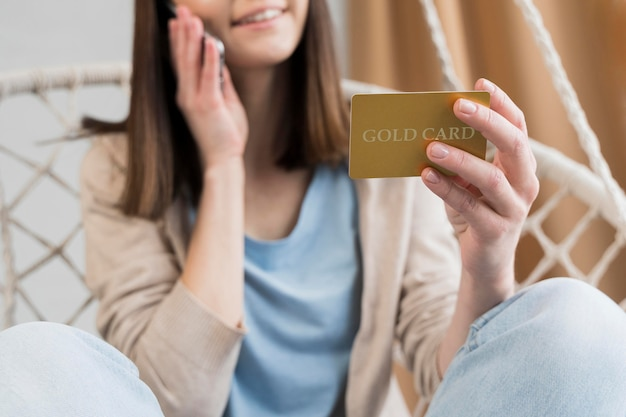 Low angle of woman holding credit card and talking on the phone