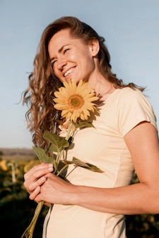 Low angle woman holding sunflower