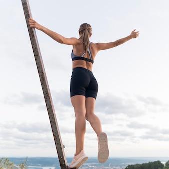 Низкоугольная женщина в спортивной одежде держит себя на металлической планке