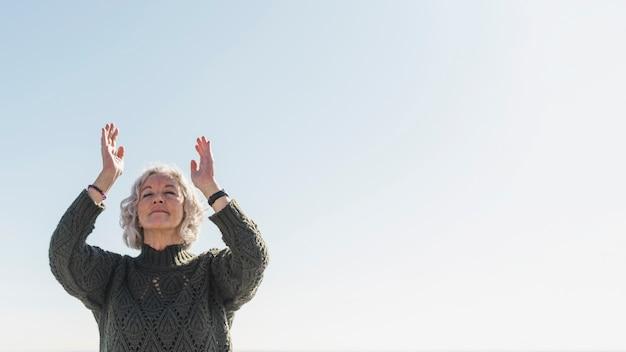 Низкий угол женщина медитирует на открытом воздухе