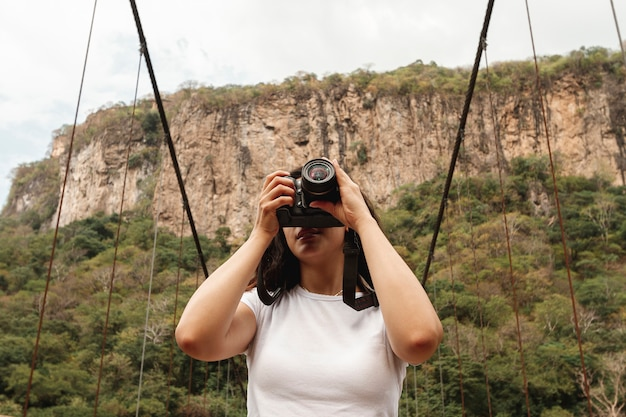 Low angle woman in nature taking photos
