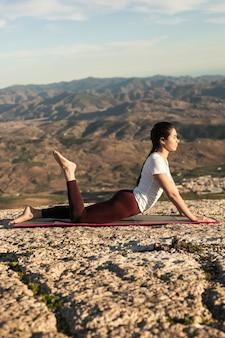 Женщина низкого угла на тренировке йоги циновки