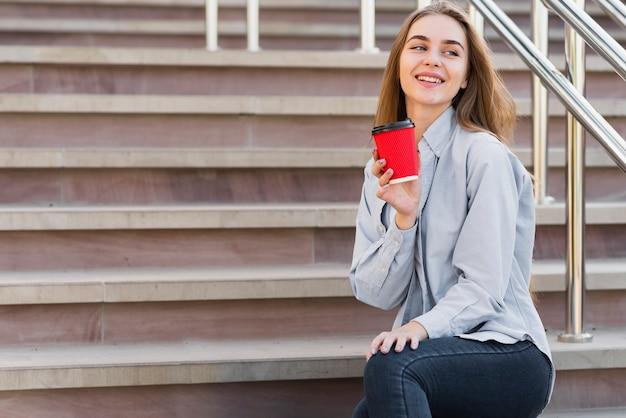 コーヒーを飲みながら階段の上の低角度の女性