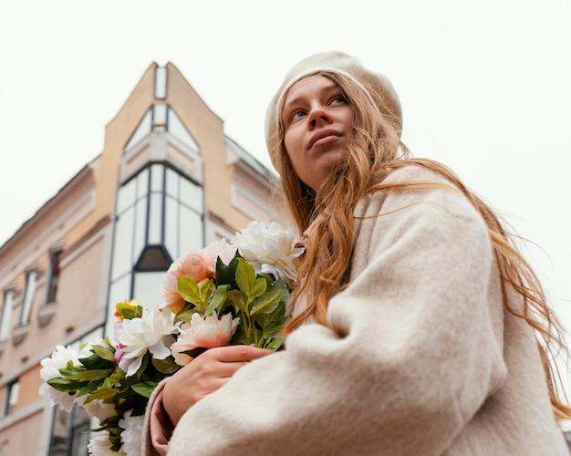 Basso angolo di donna all'aperto tenendo il mazzo di fiori in primavera