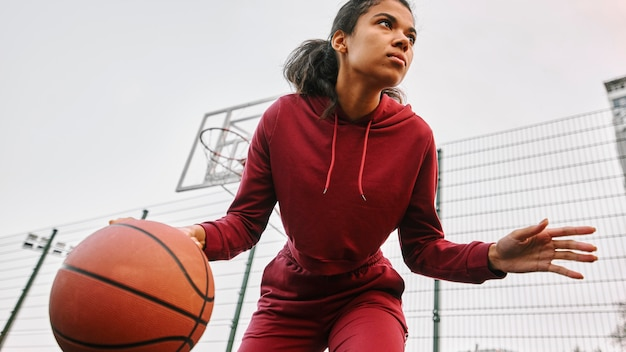 Женщина с низким углом играет в баскетбол