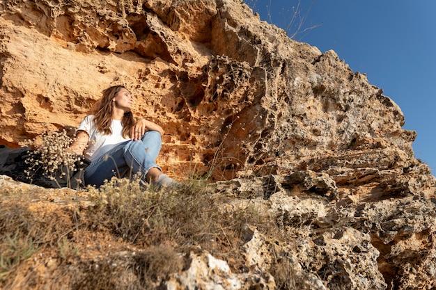 Женщина с низким углом, сидящая на берегу