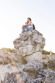 Low angle woman sitting on a rock