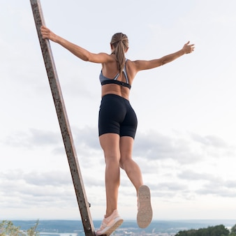 Low angle woman in sportswear holding herself on a metal bar