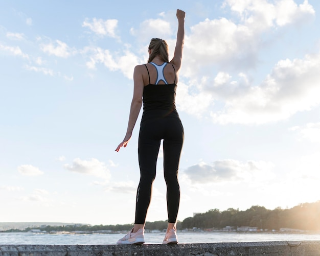 Low angle woman standing in a victorious way