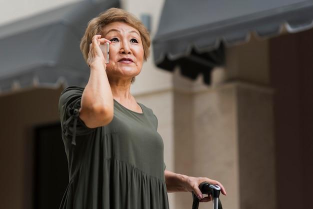 Женщина с низким углом разговаривает по телефону