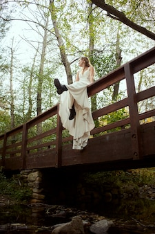 Low angle of a woman in a wedding dress with boots sitting on the railing of a bridge