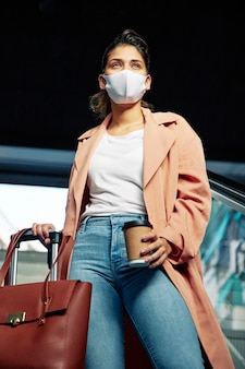 Low angle of woman with medical mask and luggage at the airport