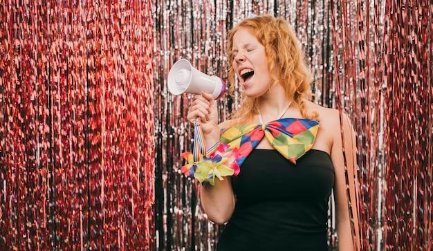 Donna di angolo basso con il megafono alla festa di carnevale