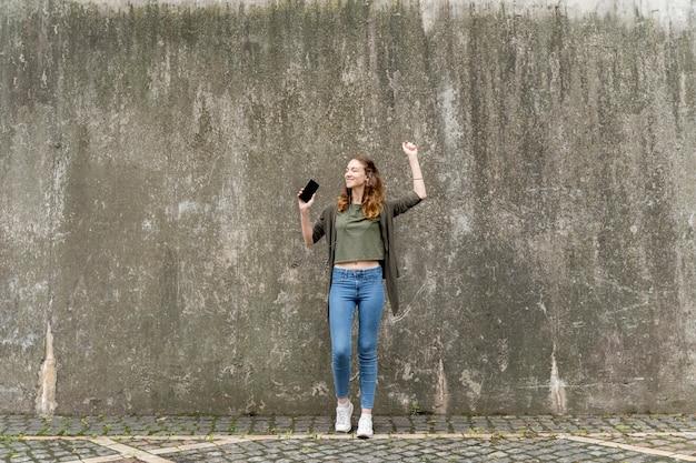 Низкий угол женщина с мобильного прослушивания музыки