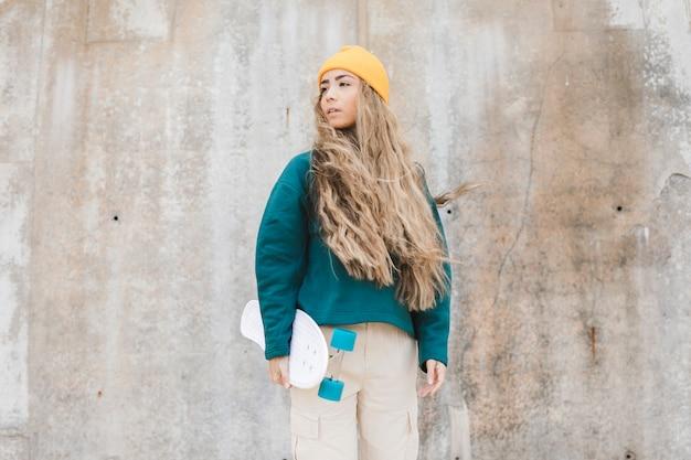 Donna di angolo basso con skateboard