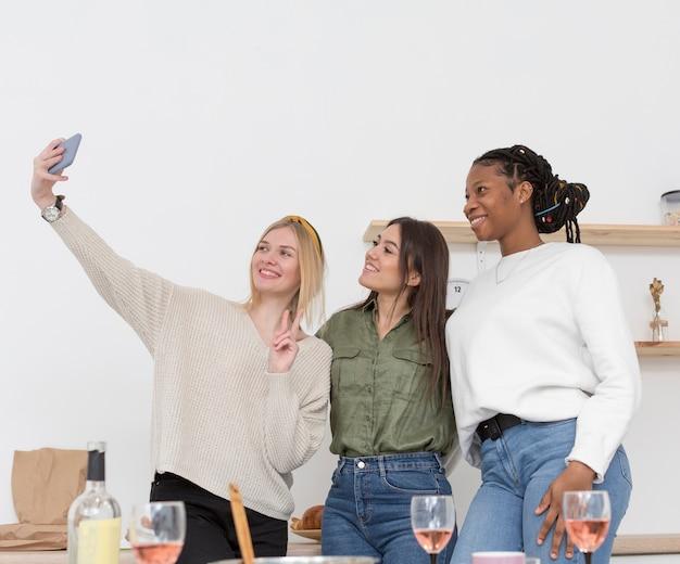Le donne di angolo basso che fanno i selfie