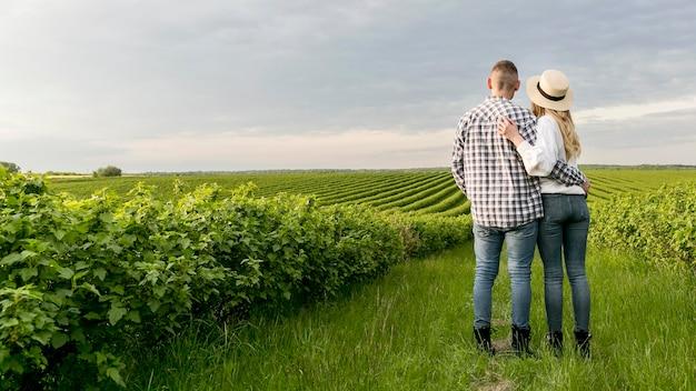 Низкий угол молодая пара на ферме