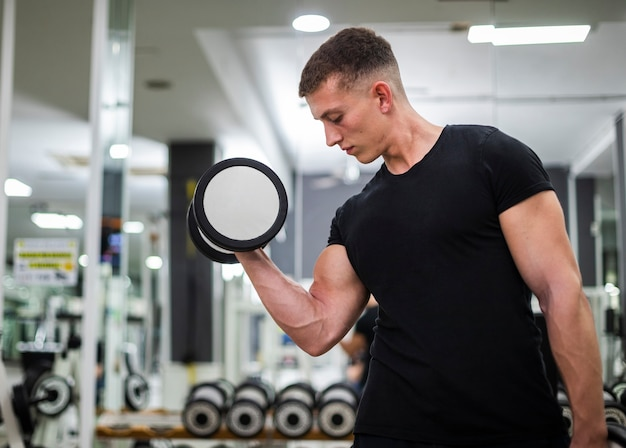 Low angle young male exercising at gym