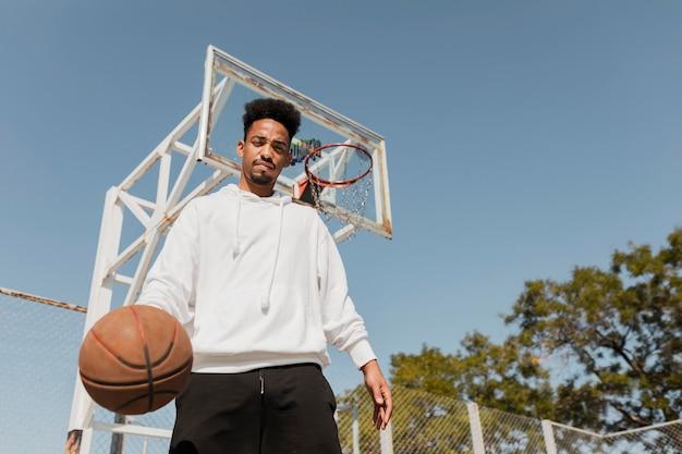 Low angle young man playing basketball