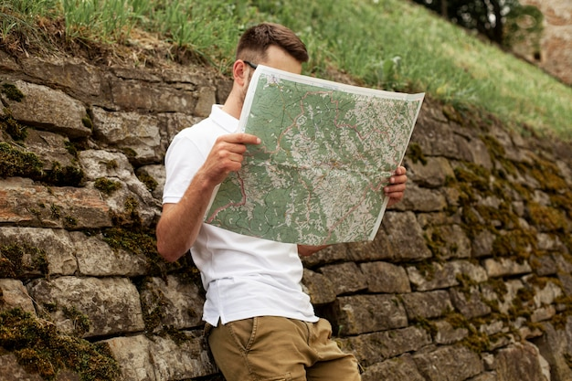 Low angle young man reading map