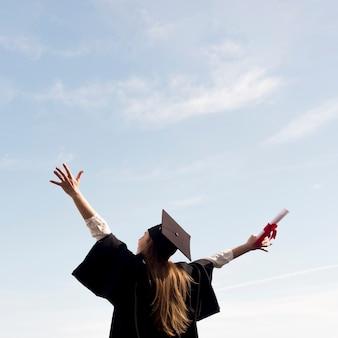 Низкий угол молодая женщина празднует свой выпускной