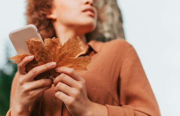 Молодая женщина под низким углом проверяет свой телефон, держа в руках сухой лист