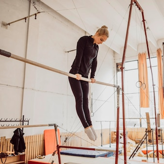 Низкий угол тренировки молодой женщины для чемпионата по гимнастике
