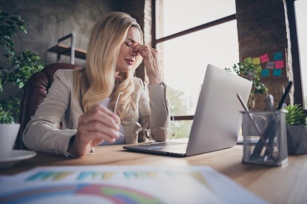 Низкий угол обзора: красивая женщина страдает от головной боли на рабочем месте и нуждается в отдыхе